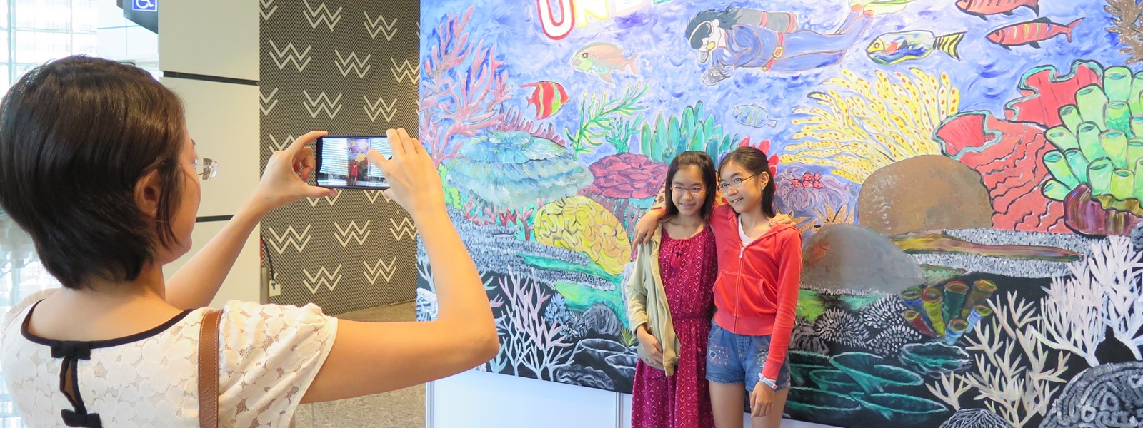 Picture of two children having a photograph take in front of AG Saño's art installation at ADEX.