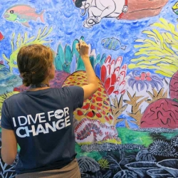 Picture of a person colouring in part of AG Saño's art installation at ADEX.