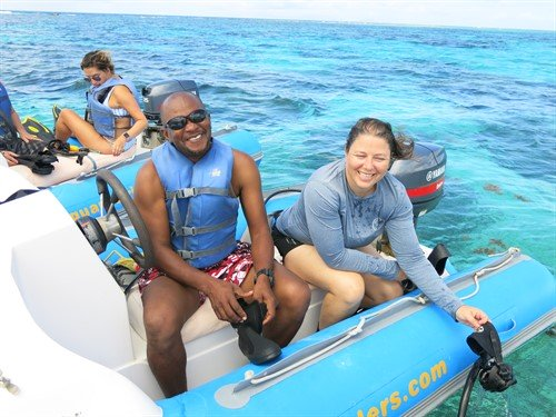 Picture of members of the Green Fins Antigua & Barbuda team on a boat, smiling at the camera.