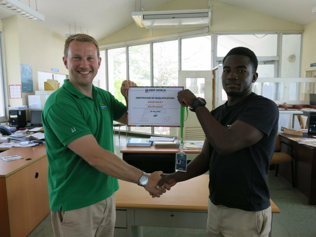 Picture of Reef-World Director JJ Harvey presenting a certificate to a member of the Green Fins team.