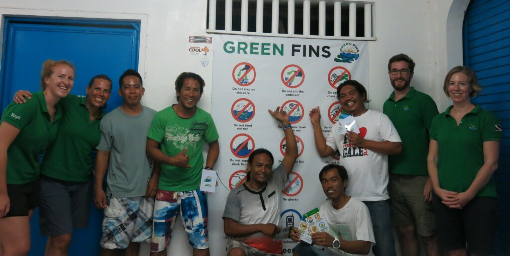 Picture of Green Fins Philippines assessors with members from dive centres in Malapascua. They are pointing at a Green Fins briefing poster.