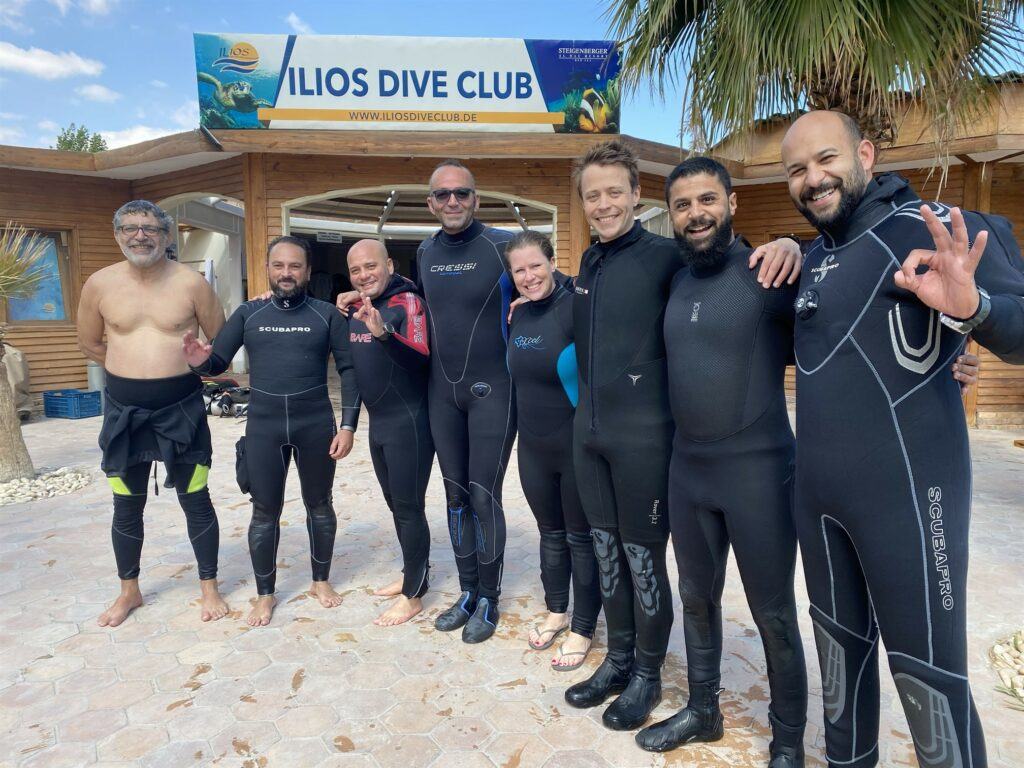 Picture of the Reef-World team with assessors standing outside Ilios Dive Club.