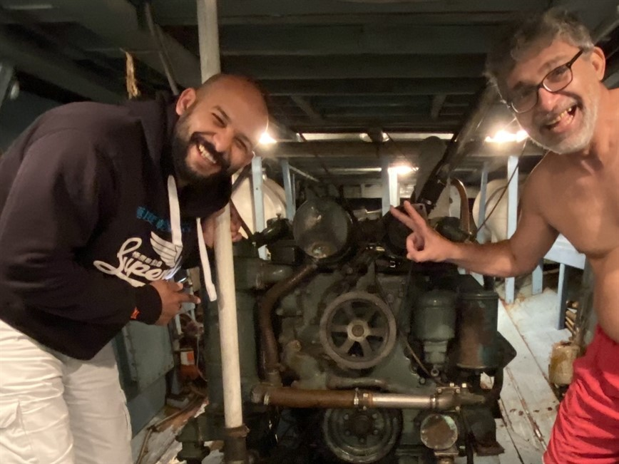 Picture of two assessors standing next to a boat engine.