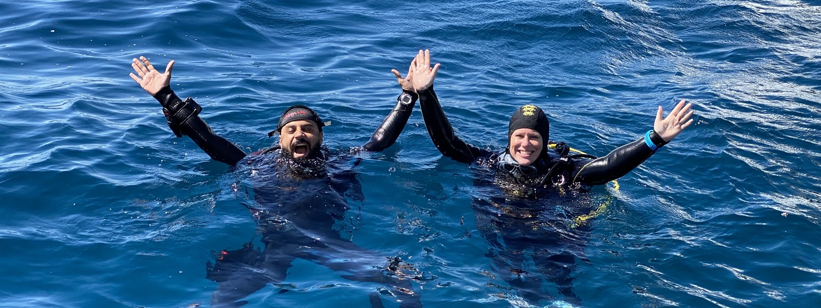 Picture of two divers in the ocean waving up at the camera.