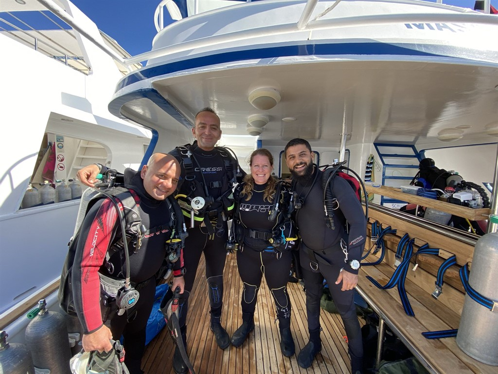 Picture of Chloe from Reef-World with three members of the Green Fins Egypt team. They are on a boat wearing diving gear. The Green Fins programme promotes good environmental standards when diving.