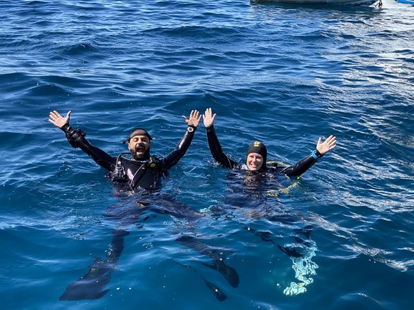 Picture of Chloe from Reef-World and a member of the Green Fins Egypt team in the water, waving up at the camera.