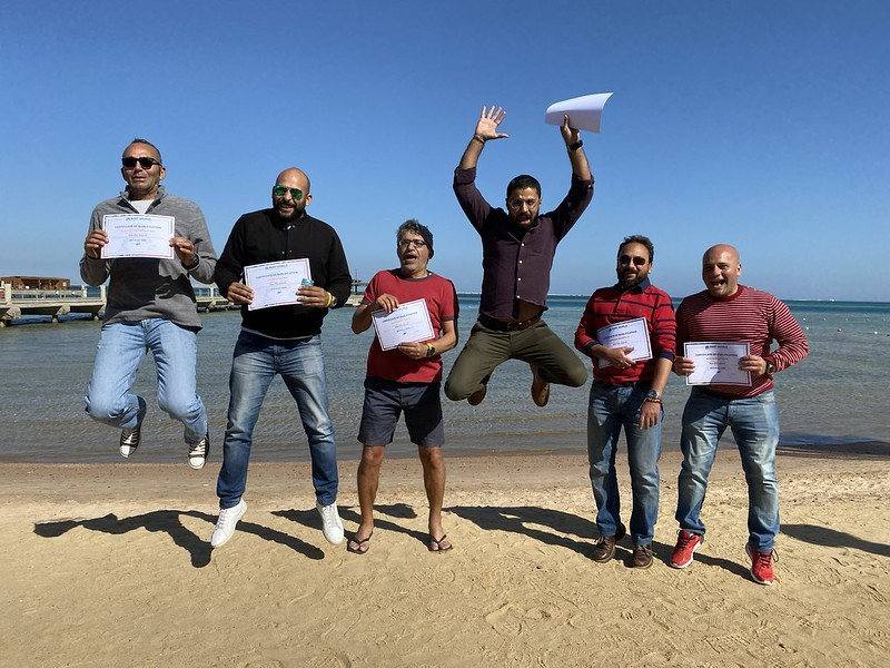 Picture of six assessors from the Green Fins Egypt team on a beach. They are holding their Green Fins certificates and jumping in celebration.