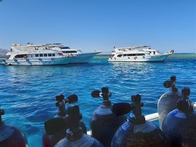Picture of boats on the sea in Egypt. There are scuba tanks in the foreground.
