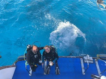 Picture of Chloe from Reef World with a member of the Green Fins Egypt team. They are in dive gear on the edge of a boat.