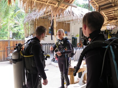 Picture of three divers during an environmental briefing at a dive centre.