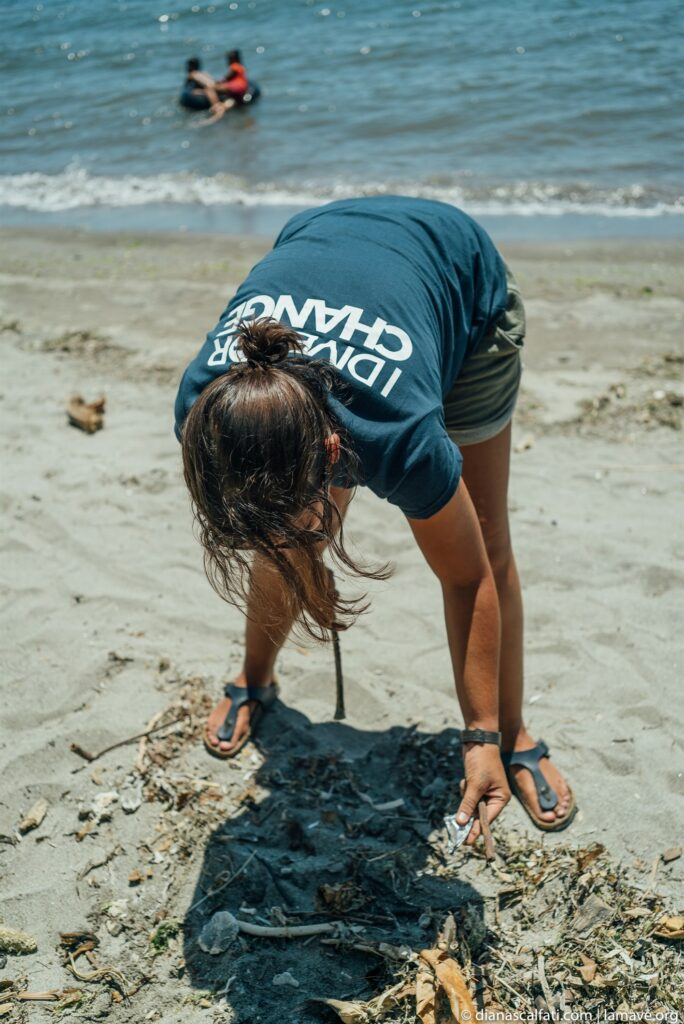 Picture of a volunteer collecting trash during a beach clean up event.