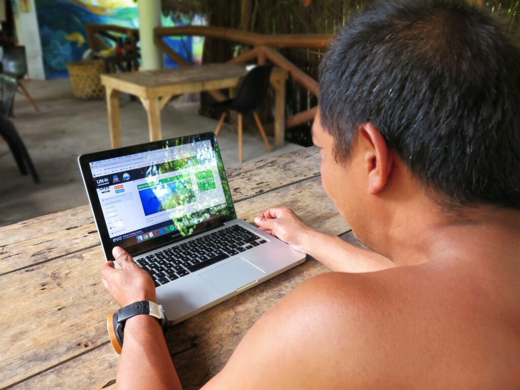 Picture of a person looking at the Green Fins Dive Guide e-Course on a laptop.