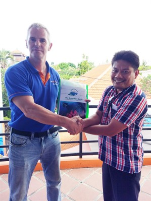 Picture of a certificate being presented  to an assessor from the Green Fins Indonesia team.