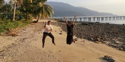 Picture of newly certified Green Fins assessors jumping for joy on the beach