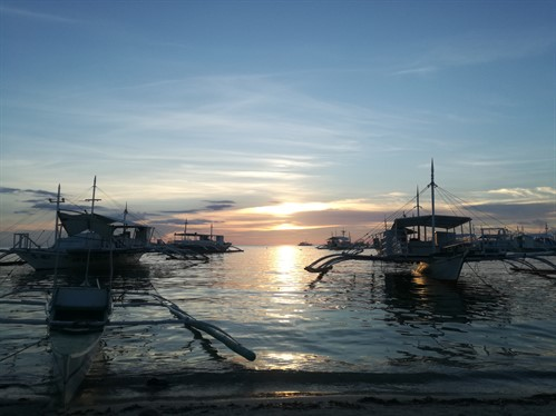 Picture of diving boats on the ocean with a sunset in the background.