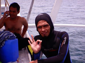 Picture of a diver on the side of a boat making the 'OK' hand gesture.