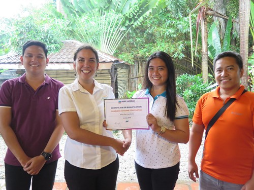 Picture of Sam from Reef-World presenting a certificate to members of the Green Fins team.