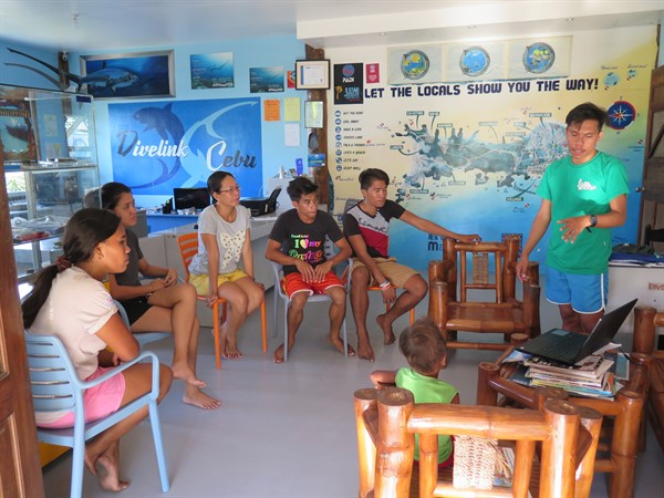 Picture of the Green Fins Philippines team meeting with members at a dive centre. A group of people is sitting around a laptop.