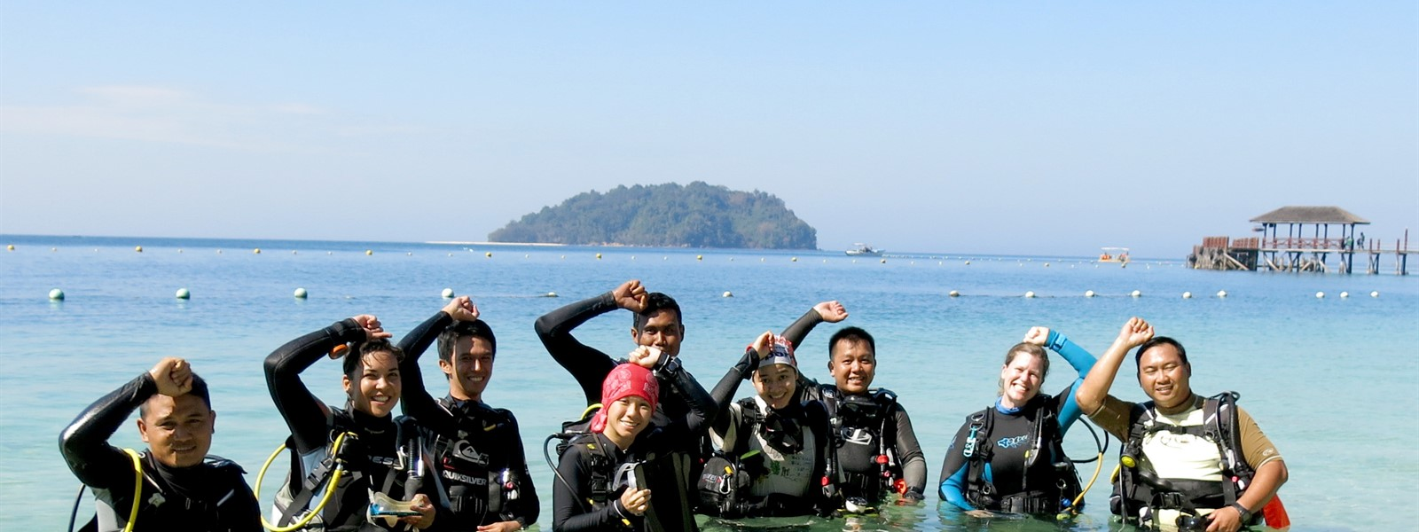 Picture of the Green Fins Malaysia team in scuba gear on a boat.
