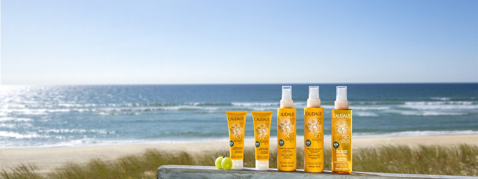 Picture of Caudalie reef-safe sunscreen products with the ocean in the background.