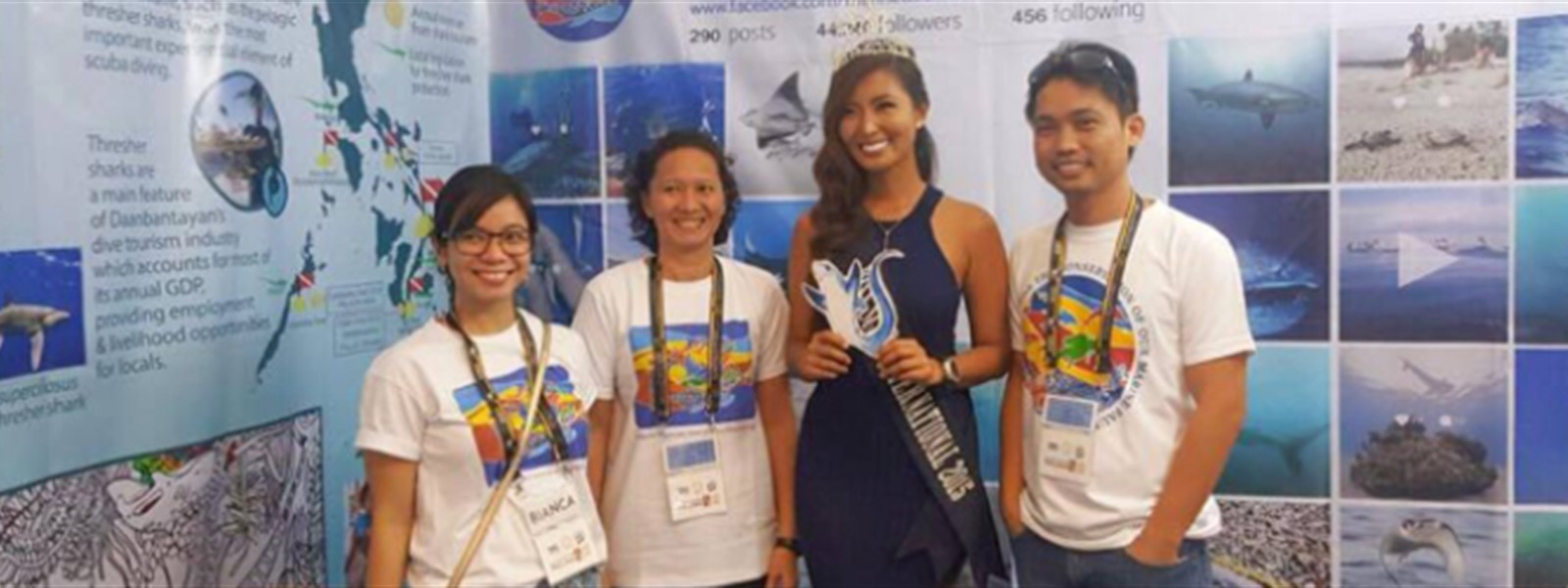 Picture of the Miss Scuba International winner standing with three other people.