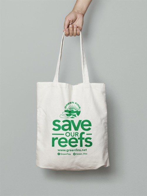 Picture of a hand holding a canvas bag with the slogan 'Save our Reefs'.