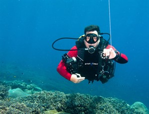 Picture of Rob from Ceningan Divers diving in the ocean holding photographic equipment.