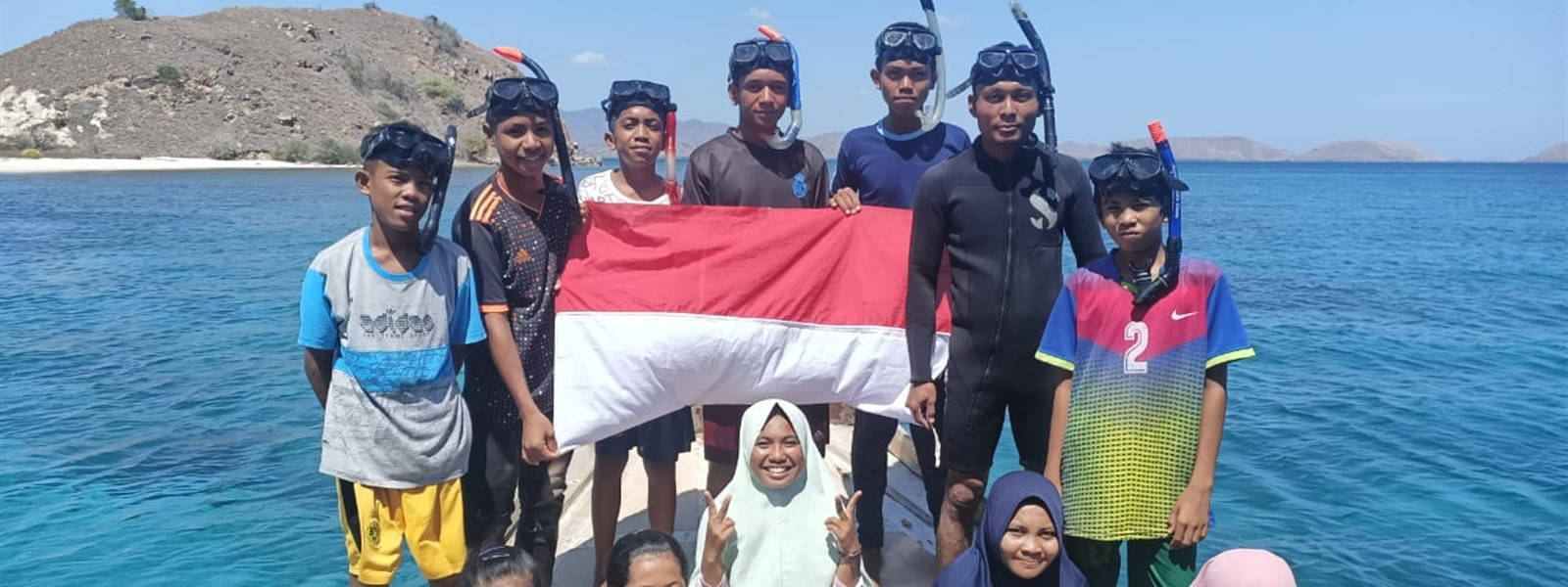 Group of divers on a boat holding the Indonesian flag.