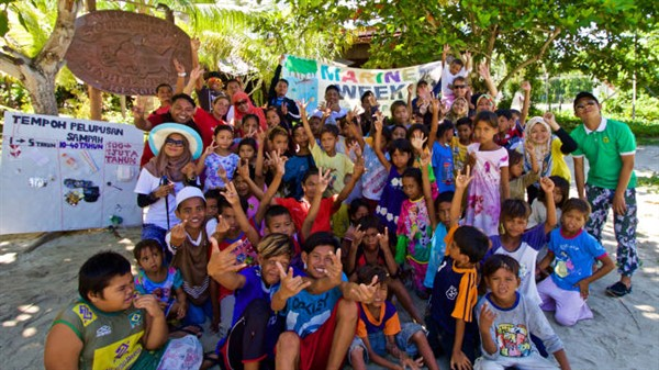 Picture of a big group of adults and children outside a dive centre. They are holding banners and waving at the camera.
