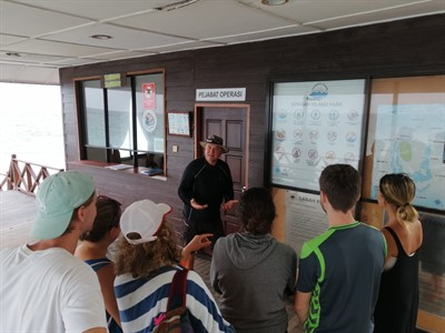 Picture of a Scuba Junkie instructor talking a group of people through the Green Fins guidelines.