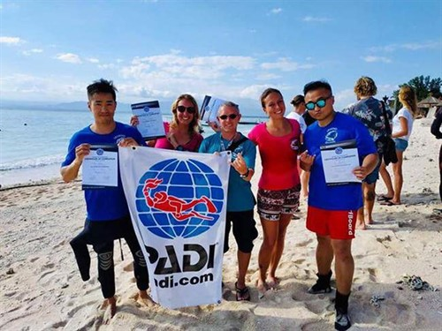 A picture of divers from Legend Diving Lembongan on the beach holding a PADI flag