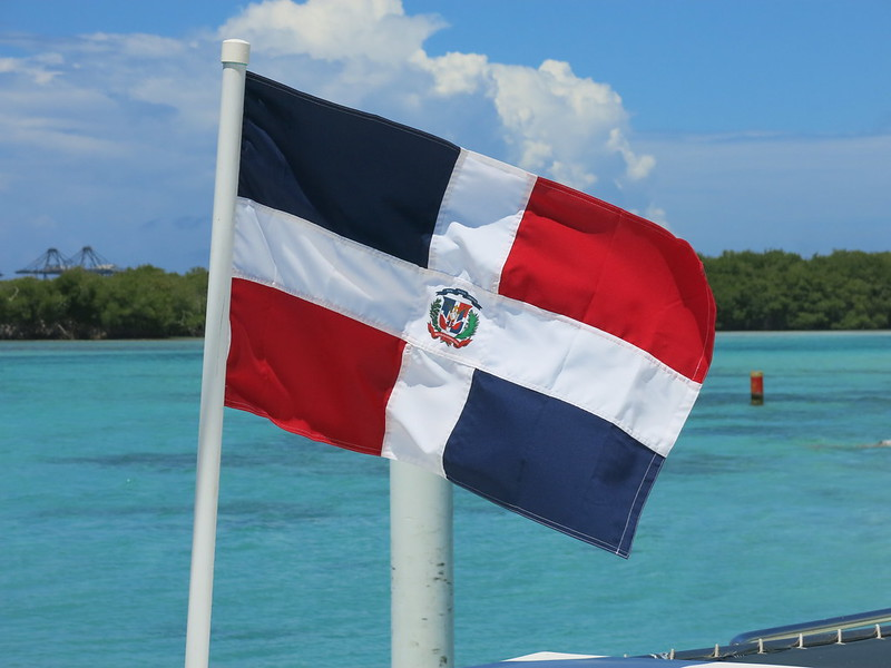 Dominican Republic flag flying with a beach in the background